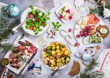 Flache Lage mit leckerem weihnachtlichen Abendtisch mit gebratenem Fleischsteak, Vorspeisen und Desserts. Ansicht von oben Ferienkonzept.