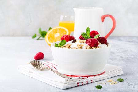 Healthy breakfast with oatmeal granola, berries and yogurt on light gray background. Copy space.