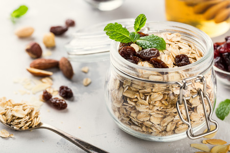 Oat flakes in glass jar with honey, raisins and nuts. Healthy breakfast concept. Stock Photo