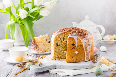 Holidays breakfast concept with copy space. Easter orthodox sweet bread, kulich and colorful quail eggs with white tulips. Stock Photo