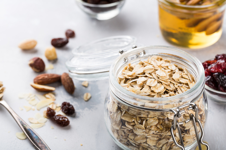 Ingredients for homemade oatmeal granola in glass jar. Oat flakes, honey, raisins and nuts. Healthy breakfast concept with copy space.