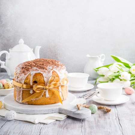 Holidays breakfast concept with copy space. Easter orthodox sweet bread, kulich and colorful quail eggs with white tulips. Copy space. Stock Photo - 91839267