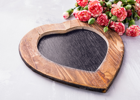 Valentines Day background with vintage slate chalk board in heart form and pink carnation flowers with copy space for text. View from above.