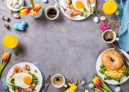 Easter breakfast flat lay with scrambled eggs bagels, orange tulips, bread toast with fried egg and green asparagus, colored quail eggs and spring holidays decorations. Top view. Copy space. Zdjęcie Seryjne
