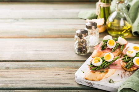 Easter breakfast or lunch with sendwich with ham, asparagus and quail eggs on white old chopping board on wooden background. Spring food concept with copy space. Stock Photo