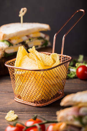 Crispy potato chips in copper basket on old wooden background served with club sandwich. Healthy fast food concept.