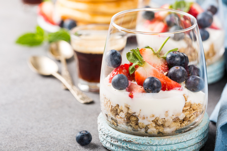 Healthy breakfast with oatmeal granola with berries and yogurt and panccakes on light gray concrete background. Healthy food concept with copy space.