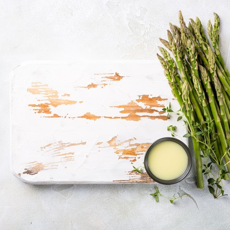 Overhead shoot with fresh green asparagus and sauce and old white wooden board. Healthy food background, copy space, top view.