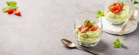 Fresh guacamole sauce from raw avocado with cherry tomatoes in glasses. Healthy vegetarian food concept with copy space.