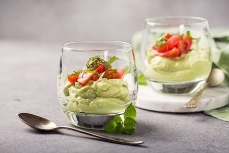 Fresh green avocado mousse with cherry tomatoes in glasses. Healthy vegan food concept with copy space. Standard-Bild
