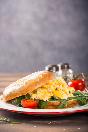 Healthy freshly baked bagel filled with scrambled eggs, rucola and fried bacon. Breakfast food. Copy space.