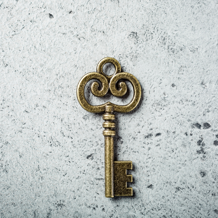 Old key on old gray concrete background.