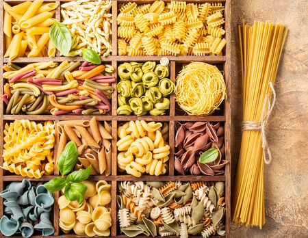 Spaghetti and assorted colorful italian pasta in wooden box. Healthy food background concept. Flat lay, top view. Stock Photo