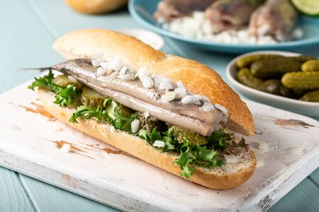 Traditional dutch snack, seafood sandwich with herring, onions and pickled cucumber. Broodje haring. Close up. Foto de archivo