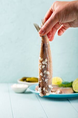 Female hand holding herring with onion, traditional dutch delicacy called hollandse nieuwe on turquoise background. European food concept with copy space.