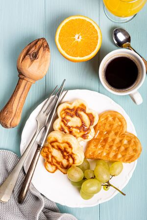 Overhead shoot of breakfast with fresh hot waffles hearts, flowers pancakes with fruits on turquoise background, top view, flat lay. Healthy food concept.