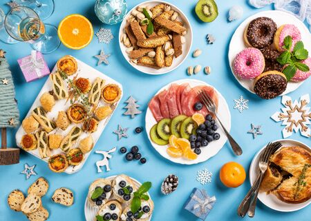 Overhead shoot of Chtistmas holiday food concept background with dinner party table over blue, top view, flat lay, bokeh Foto de archivo - 133589625