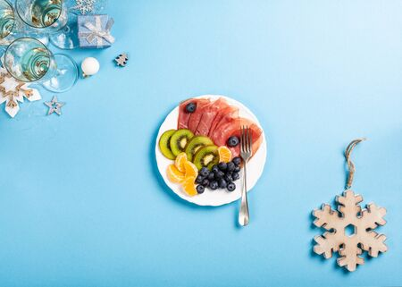 Christmas composition with meat, fruit, champagne and decorations on blue. Holidays food background with copy space for text. Top view. Flat lay. Foto de archivo - 133589752