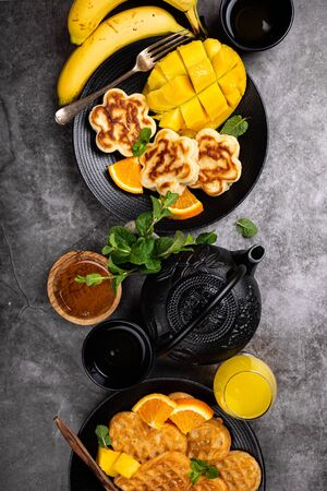 Healthy breakfast background with fresh hot waffles hearts, pancakes flowers with berry honey and exotic fruits over gray, top view, flat lay. Healthy food concept with copy space. Foto de archivo - 133589794
