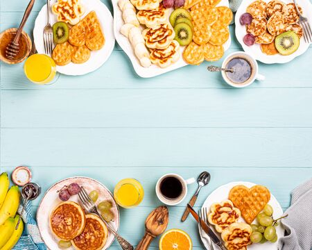 Food background with healthy breakfast with fresh hot waffles hearts, pancakes flowers with berry jam and fruits on turquoise table, top view, flat lay, copy space. Foto de archivo - 133589923
