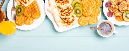 Food background with healthy breakfast with fresh hot waffles hearts, pancakes flowers with berry jam and fruits on turquoise table, top view, flat lay, copy space. Banner. Foto de archivo - 133589925