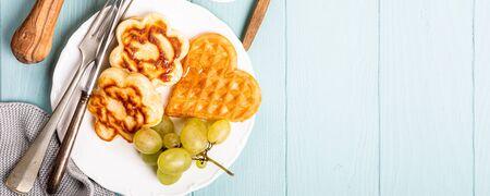 Healthy breakfast with fresh hot waffles hearts, pancakes flowers Foto de archivo - 134471948