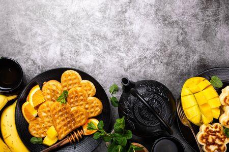 Healthy breakfast with fresh hot waffles hearts, pancakes flowers Foto de archivo - 134472483