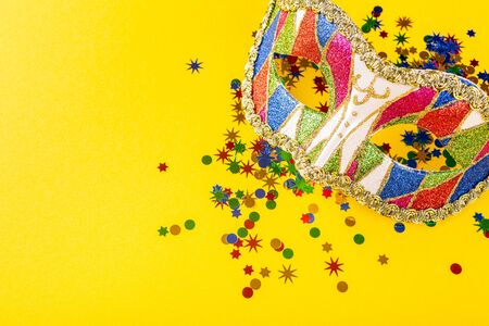 Festive yellow background with colorful carnival mask. Foto de archivo - 134473562
