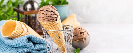 Delicious coffee or chocolate ice cream in waffle cone for dessert. Summer healthy food concept, lactose free. Copy space. Banner 스톡 콘텐츠