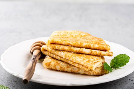 Delicious Tasty Homemade crepes or pancakes with honey, honey and mint on white plate. Healthy breakfast concept, gluten free. Copy space.
