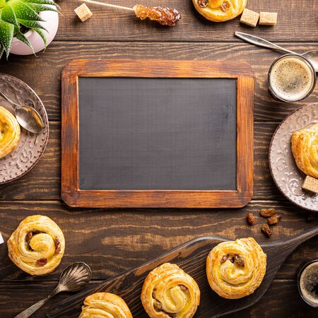 Food background for cafe menu with fresh pastry sweet swirl buns with raisins for breakfast or brunch and coffee, with black chalkboard. Top view, copy space.
