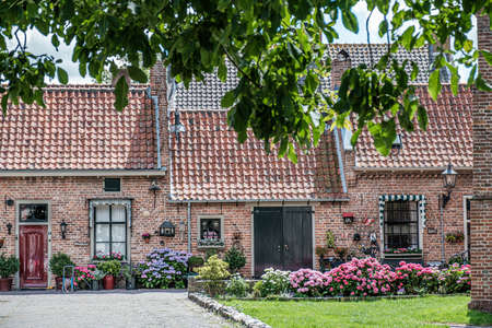 Traditional old terraced houses with front yard in the Netherlands in small town Buren, July 2020