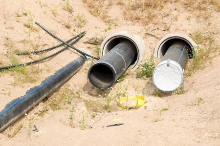site preparation: Plastic pipes being placed under ground for water supply. Temporarily resting in ditch waiting to be connected and put in Place.