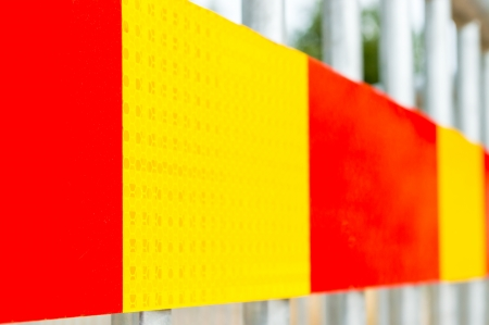 Red and yellow warning tape on aluminium bars photo