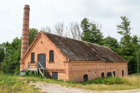 Old abandoned brick factory with chimney and wooden stairs on outside.