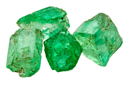 uncut: Four rich green emerald crystals on white