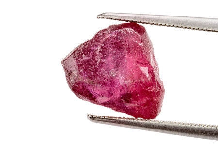 One red ruby crystal held by tweezers