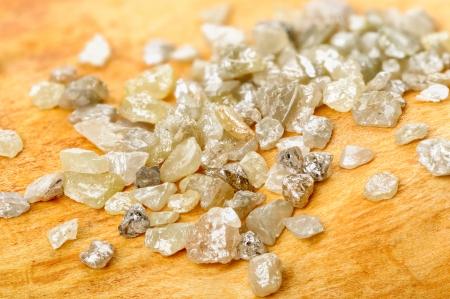 materia prima: Un montón de blanco gris diamantes en bruto y ásperas en madera de abedul Foto de archivo