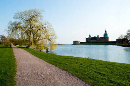 Gravel walkway under big tree in early spring  Kalmar castle in background  Stock Photo