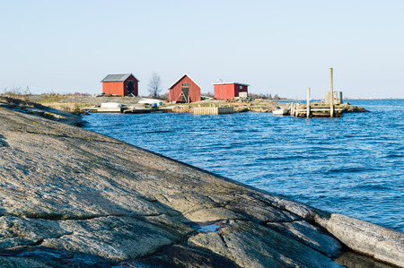Three small boathouses in the coastline  Granite rock in foreground  Blue sea in front Morning sunshine  Stock Photo