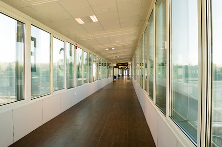 Built in walkway in train station. Windows on sides and long corridor.