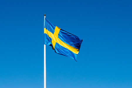 Swedish flag against blue sky on white flagpole photo