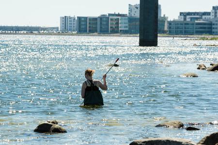 botas altas: Kalmar, Suecia - 26 de mayo 2014: Mujer en agua con red de anillos de examinar el Mar Báltico para la educación ecológica.