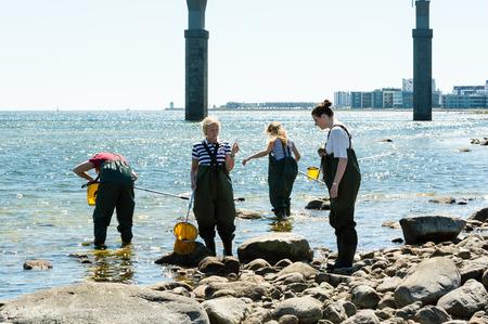 botas altas: Kalmar, Suecia - 26 de mayo 2014: Grupo de personas en el agua sobre la ecología excursión. Puente en el fondo.