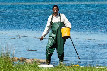 botas altas: Kalmar, Suecia - 26 de mayo 2014: Varón en agua con red de anillos de encontrar animales.