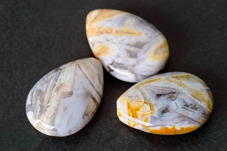 teardrop: Three needle agate teardrop shaped beads on black stone.