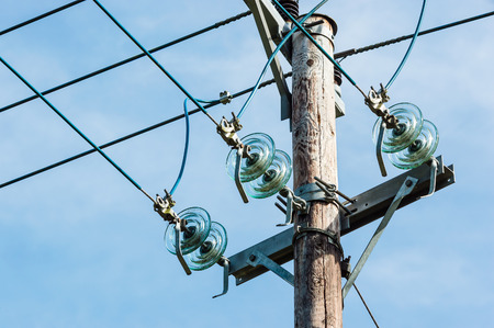 Old wooden power line pole with insulators. Blue sky in background. Stock Photo