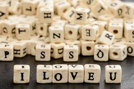 i love u: I love u �crit en perles de lettres en bois sur la plaque de pierre noire. perles de lettres en arri�re-plan.