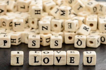 i love u: I love u written in wooden letter beads on black stone plate. Letter beads in background. Stock Photo