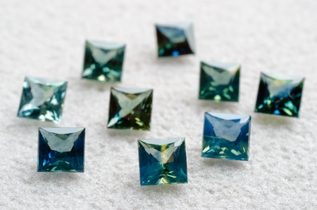 greenish blue: Greenish blue sapphires in princess cut on rough mat.
